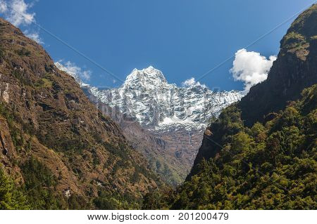 Snowy Mountain Peak Between Rocky Mountain And Wooded Hill In Sagarmatha National Park, Himalayas, N