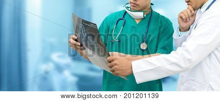 Doctor And Surgeon Looking At X-ray Film