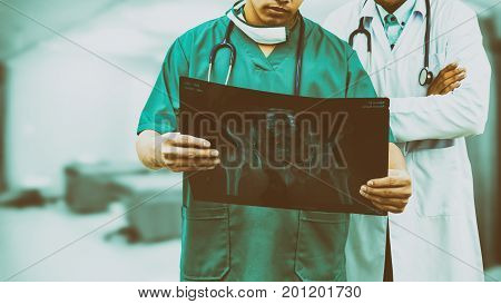 Surgeon And Doctor Looking At X-ray Film.