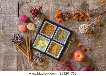 Tray of autumn spices in woodsy earthy colors on rustic wood table candles cinnamon apple and fall plants surrounding