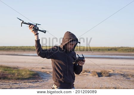 man hold in hand dron and remote controler, young man prepare quadrocopter to fly in desert