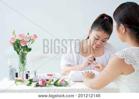 Professional Asian manicurist provides service to female client