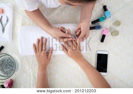 Manicurist cutting off cuticles of female client