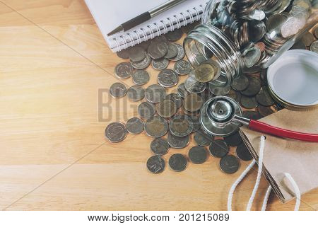 idea saving money and stethoscope on coins for healhcare medical finance concept