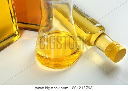 Beaker and bottles with cooking oil on white background