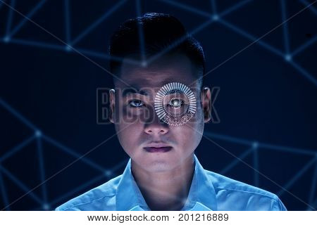 Face of Vietnamese man using modern technology to scan his retina