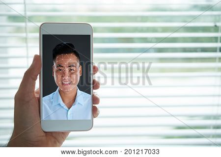 Asian man using biometric verification to get access to his smartphone