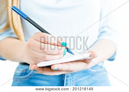 Close-up shot of crop female hands holding pen and writing in notebook on white background.