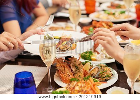 Hands of woman putting shellfish mussels to the plate of her husband at festive dinner