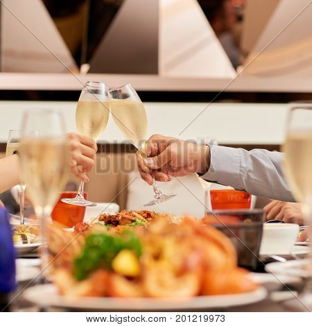 Hands of couple cheering with champagne flutes