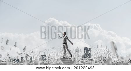 Man in casual wear keeping hand with book up while standing among flying letters with cloudly sky on background. Mixed media.
