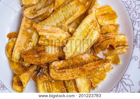 Sweet banana crisps Asian style dessert made from banana slide fried with sugar.