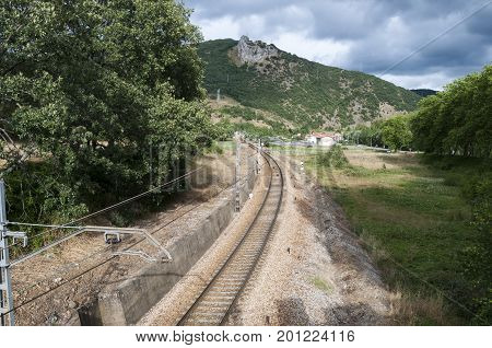 Iberian gauge railway track between Leon and Gijon on its way through La Pola de Gordon, Leon Province, Spain. In the background can be seen the town of Puente de Alba