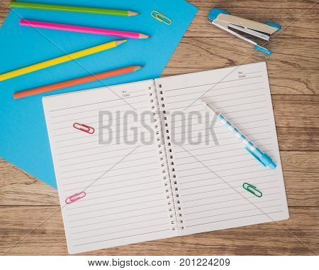 Notebook, Paper, Stapler, Pen And Other On Wooden Plank.