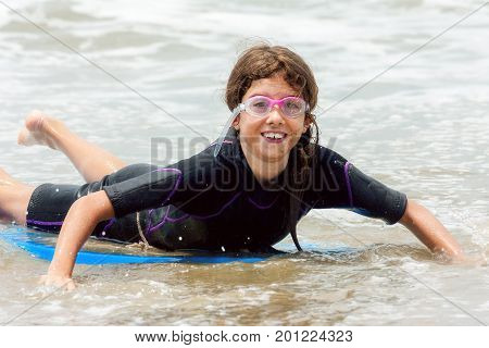 A young girl lays on a boogie board in very shallow water at the beach. She is wearing a wet suit and goggles.