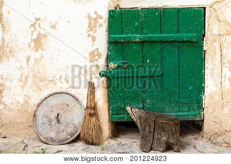 Clay wall with wooden door of old rural barn and metal cover and used broom beside