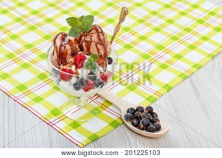 Chocolate And White Ice Cream In A Glass With Raspberry And Currant Berries And Mint Leaves On Check