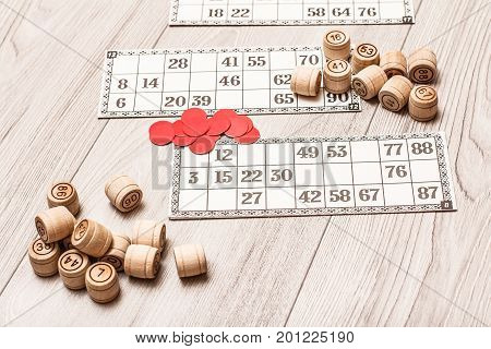 Board Game Lotto On White Desk. Wooden Lotto Barrels, Game Cards And Chips