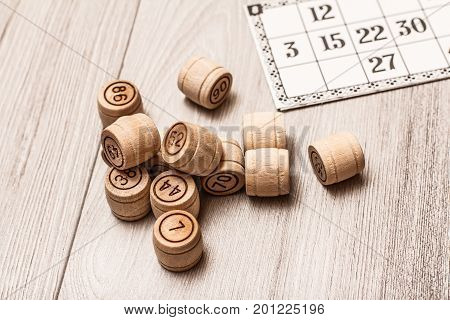 Board Game Lotto On White Desk. Wooden Lotto Barrels And Game Card