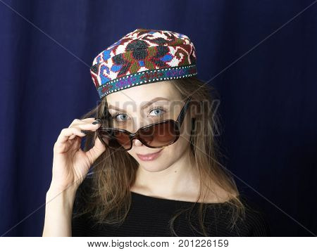 A young woman in colorful hat with inquisitive look over the sunglasses. Studio portrait