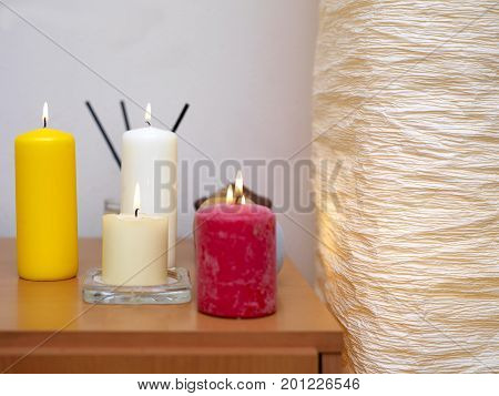 Decorative lamp and scented candles placed on a table cropped sot with particular focus