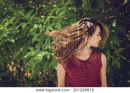Beautiful Vietnamese young woman with flattering hair standing at green bush