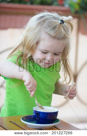 Boy child mixing sugar in blue cup. Little kid boy making tea. Childhood and baby care concept. Child boy with blond long hair mixing sugar with teaspoon. Healthy breakfast for child.