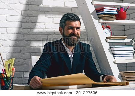 Teacher And School Supplies In Classroom. Man With Beard