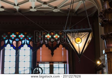 Antique Colorful Glass Chandelier In Bookshop And Large Windows In Background