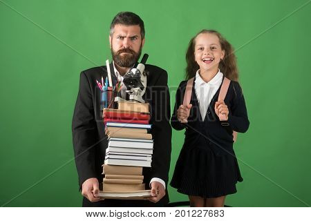 Kid And Dad Hold Pile Of Books With School Supplies