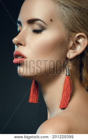 beautiful young woman in studio on a dark background. Fashion portrait of a blonde with red earrings