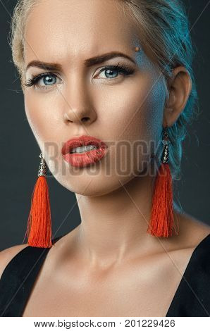 frowning blonde trendy studio portrait with red earrings