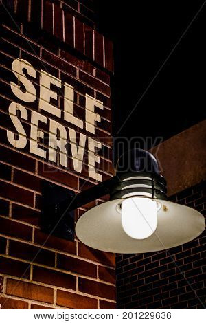 self serve sign on brick wall with light vertical