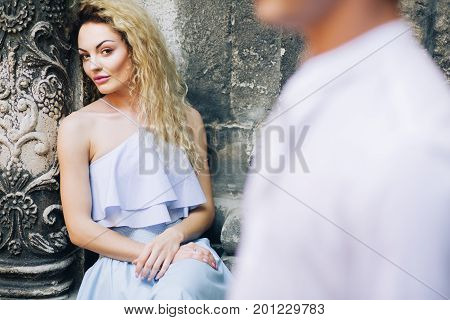 Gorgeous Blonde Woman In Elegant Blue Dress Looking At Man In Hipster Shirt Near Old Cathedral Landm