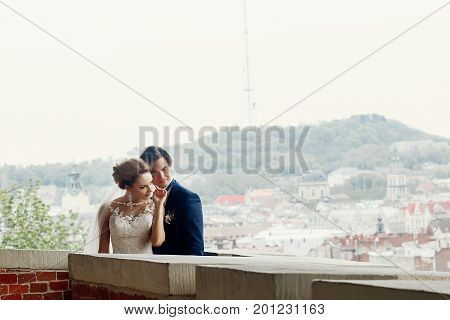 Happy Newlywed Couple On Castle Wall, Cityscape And Hill In The Background, Stylish Newlyweds Portra