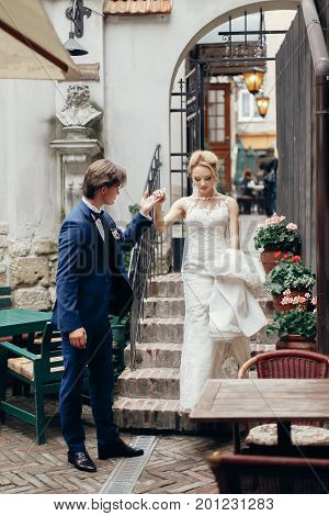 Newlywed Husband Offering His Hand To Beautiful Wife On Stairs In Paris, Happy Newlywed Couple On A