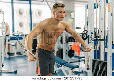 close up photo of sport man training on Fitness-station. Guy has strong hands. He working out to develop strength, develop definition of muscles, become cut, shredded.