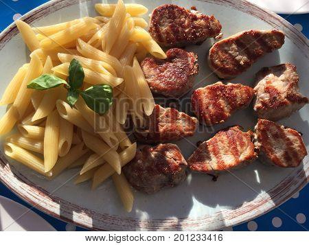 Gegrilltes Fleisch mit Pasta auf antik anmutendem Teller