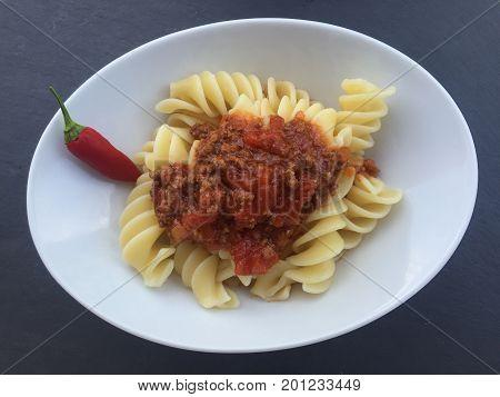 Fusilli Pasta mit Bolognese Tomatensauce in weissem Teller auf schwarzem Hintergrund