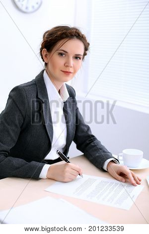Business woman looks like yulia tymoshenko is sitting at the table and working in  white colored office . Ukrainian hair styling. Independence and success concept.