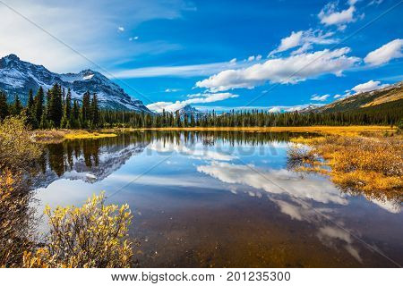 Sky and clouds reflected in smooth water in the lake. The concept of active tourism and ecotourism. Rocky Mountains on a sunny day