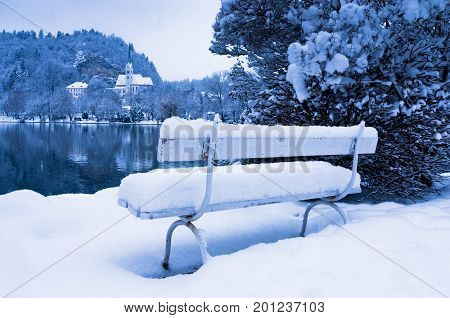 Romantic white bench covered with snow on a lake Bled in Slovenian Alps, Slovenia