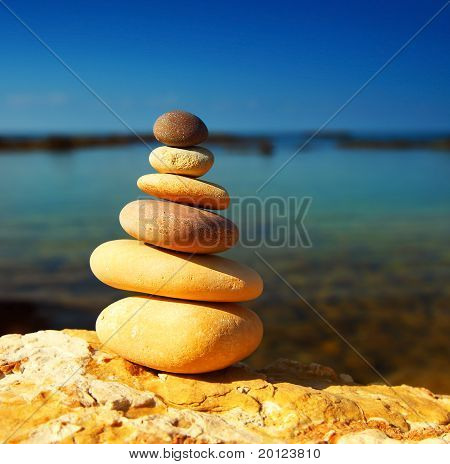 Zen spa balance stones over blue calm sea background conceptual image of relaxation & vacation poster