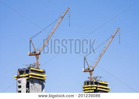 Cranes manufacturing construction work. Close-up panorama City