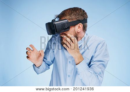 A young guy with a beard on a blue background with virtual reality glasses.