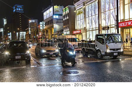 JAPAN, TOKYO, APRIL, 02, 2017 - Night traffic on the streets of Tokyo near Shinagawa Station during the rain. Shinagawa-eki is a major railway station in Tokyo, Japan.