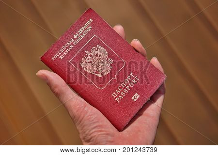 Male hand holding a Russian passport with captions Passport and Russian Federation in Cyrillic alphabet