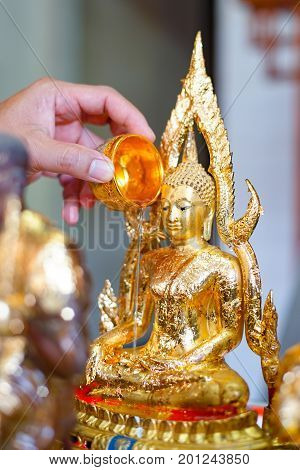 Hand-held small bowl and then water the Buddha image in Songkran day to be auspicious on New Year's Day of Thailand on April 13 every year. Clean and put a new golden leaf on.