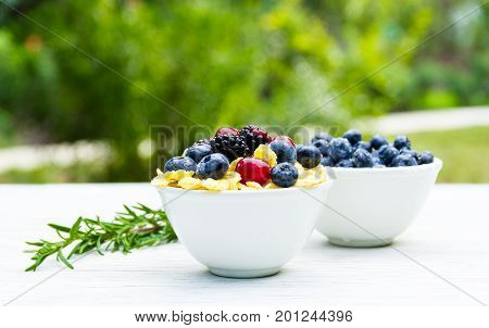 Delicious healthy breakfast in the garden. Corn flakes and forest berries. Blueberries and blackberries