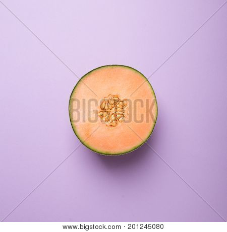 Tasty fresh yellow appetizing cut melon on bright pastel background fashion minimalism top view above